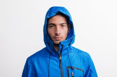 Portrait of a young serious hispanic man with blue anorak in a studio.. Portrait of a young serious hispanic man with blue anorak in a studio, with a hood on stock photos