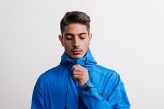 Portrait of a young serious hispanic man with blue anorak in a studio. Portrait of a young serious hispanic man with blue anorak in a studio, looking down stock photo