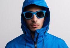 Portrait of a young serious hispanic man with blue sunglasses and anorak in a studio. Portrait of a young serious hispanic man with blue sunglasses and anorak royalty free stock photo