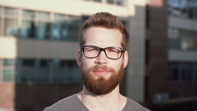 Portrait of young serious man with beard and glasses standing in front of sun, linking. Businessman stands near office. stock video