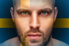 A portrait of a young serious man, in whose eyes is reflected the national flag stock image
