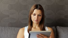 Portrait of young serious woman looking at digital tablet. Woman with tablet pc sitting on sofa. Woman using tablet stock video footage