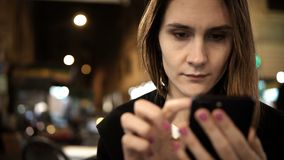 Portrait of young serious woman sitting in the city centre in the evening and using the smartphone with touchscreen. Attractive female spending time in stock video footage