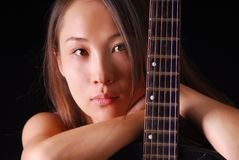 Portrait of a young sexual woman with вrown,hair bare shoulders and guitar neck on a black background Stock Photos