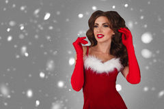 Portrait of young, sexy and beautiful woman in christmas dress with snow. Grey background. Stock Image