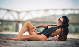 Portrait of young sexy brunette girl in black low-cut swimsuit lying on the beach with a   bridge in background. Sensual woman Stock Images