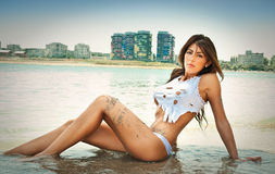 Portrait of young sexy brunette girl in white bikini and wet t-shirt at the beach. Sensual attractive woman in water wearing bikini and long legs . Woman with Royalty Free Stock Images