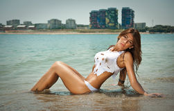 Portrait of young sexy brunette girl in white bikini and wet t-shirt at the beach. Sensual attractive woman in water wearing bikini and long legs . Woman with Stock Photo