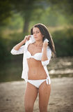Portrait of young sexy brunette girl in white swimsuit and male shirt posing on a beach with a forest in background Stock Images