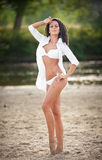 Portrait of young sexy brunette girl in white swimsuit and male shirt posing on a beach with a forest in background Stock Photos