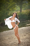 Portrait of young sexy brunette girl in white swimsuit and male shirt posing on a beach with a forest in background Royalty Free Stock Photo