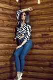 Portrait of young sexy dark-haired model wearing skinny high-waisted jeans, striped tied up shirt, choker and golden sneakers Stock Image