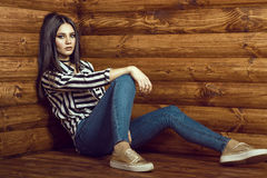 Portrait of young sexy dark-haired model wearing skinny high-waisted jeans, striped tied up shirt, choker and golden sneakers Royalty Free Stock Photo