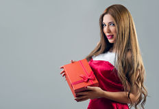 Portrait of young, sexy female Santa with a gift box Royalty Free Stock Photos