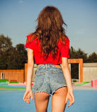 Portrait of a young girl with long dark hair from the back of a summer evening in a skate park. Close up. Stock Images