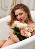 Portrait of a young sexy girl with long hair with a bouquet of roses, her long earrings Stock Photography