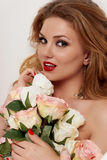 Portrait of a young sexy girl with long hair with a bouquet of roses, her long earrings Stock Image