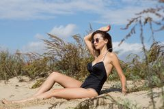 Portrait of young sexy girl lying on sand on a background of tall grass and sky. She wearing black swimwear and sunglasses. Portrait of a young sexy girl lying Stock Image