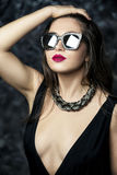 Portrait of a young sexy and seductive brunette woman with red lipstick in black dress and sunglasses. Portrait of a young sexy and seductive brunette woman with Stock Images