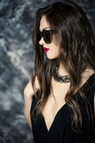Portrait of a young sexy and seductive brunette woman with red lipstick in black dress and sunglasses. Portrait of a young sexy and seductive brunette woman with Stock Photography
