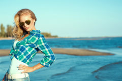 Portrait of young sexy suntanned smiling blond wearing mirrored heart shaped sunglasses and checked blue shirt standing at the sea. Side with the hand on her hip Royalty Free Stock Image