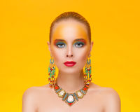 Portrait of a young sexy woman in jewelry. On an gold background Royalty Free Stock Photos