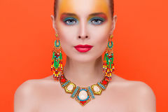 Portrait of a young sexy woman in jewelry. On an orange background Royalty Free Stock Image