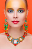 Portrait of a young sexy woman in jewelry. On an orange background Royalty Free Stock Photos