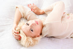 Portrait of young woman lying on  bed Stock Images