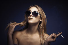 Portrait of young sexy woman while smoking cigarette Stock Images