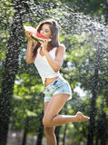 Portrait of young woman in spray of water with watermelon. She has a good gentle skin, her hair flying, and she smiles royalty free stock image