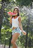 Portrait of young sexy woman in spray of water with watermelon.She has a good gentle skin, her hair flying, and she smiles Stock Photography