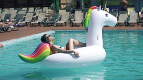 Portrait of young woman sunbathing on an inflatable mattress a unicorn in an outdoor pool. beautiful girl in. Young woman in swimsuit sunbathing lying on an stock video footage