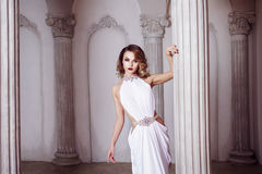 Portrait of young sexy woman in a white dress, luxurious hall with columns Stock Image
