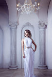 Portrait of young sexy woman in a white dress, luxurious hall with columns Stock Photos