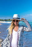Portrait of a young sexy woman with white hat and sunglasses walking on white sand beach a tropical Bali island at sunny Royalty Free Stock Photo