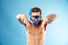 Portrait of a young shirtless guy wearing snorkel and goggles. Showing swimming gesture with hands isolated over blue Stock Image