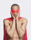 Portrait of young shirtless man in superhero costume with hands on face against gray background Stock Photography