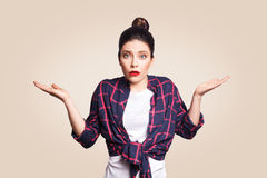 Portrait of young shocked brunette woman with casual style looking desperate or panic, keeping mouth open. And making helpless gesture with her hands, doesn`t Stock Images