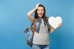 Portrait of young shocked excited woman student with backpack holding white heart with copy space and clinging to head royalty free stock photo