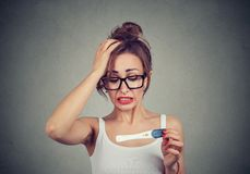 Portrait of a young shocked woman with pregnancy test royalty free stock image