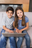 Portrait of young siblings using laptop in living room Royalty Free Stock Photography