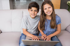 Portrait of young siblings using laptop in the living room Royalty Free Stock Image