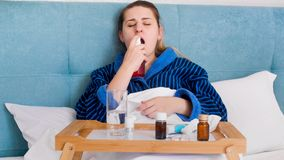Portrait of young sick woman with sore throat lying in bed and using medicine spray. Portrait of sick woman with sore throat lying in bed and using medicine stock image