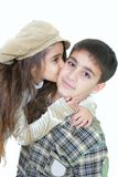 Portrait of young sister kissing elder brother. Over white Royalty Free Stock Photography