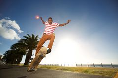 Young skateboarder doing tricks on the road. Portrait of a young skateboarder doing tricks and jumping on the road by the beach Royalty Free Stock Photography