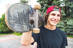 Portrait of a young skater with his favorite skateboard. Portrait of a young long-haired skater in a cap with his favorite skateboard on his shoulder Stock Photos
