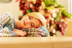 Portrait of a young sleeping woman on the table Stock Image