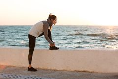 Portrait of young slim sport woman tying shoelace at the morning Stock Image