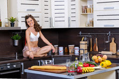 Portrait of a young slim woman in lingerie in the kitchen Royalty Free Stock Images